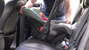 Kindermädchenplatzbaby-Sicherheitsstuhl auf hinterem Autositz und befestigen sich 4K stock footage