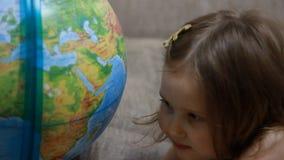 Kinderm?dchen, das mit Kugel spielt Baby studiert Geografie und eine Karte der Welt stock footage