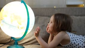 Kinderm?dchen, das mit Kugel spielt Baby studiert Geografie und eine Karte der Welt stock video