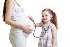 Kindermädchen, das auf schwangeren Mutterbauch hört Lizenzfreie Stockfotos