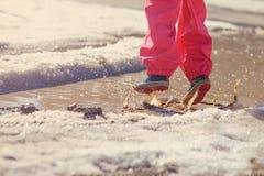 Kindermädchen, das im Frühjahr Pfütze mit großem Spritzen springt Stockfotografie
