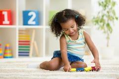 Kindermädchen, das Spielwaren am Kindergartenraum spielt Lizenzfreies Stockbild
