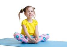 Kindermädchen tut die Gymnastik, die im Schmetterling sitzt Lizenzfreie Stockbilder
