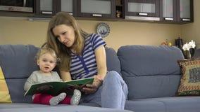Kindermädchenfrauengeschichtenerzählen las Buch für Kind am Kindergarten bei der Arbeit stock footage