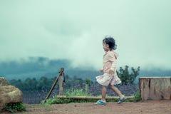 Kindernettes kleines Mädchen, das in den Garten Regen nachläuft Stockbilder