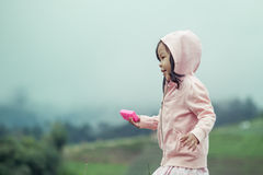 Kindernettes kleines Mädchen, das in den Garten Regen nachläuft Lizenzfreie Stockfotografie