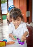 Kindernettes kleines Mädchen, das mit Lehm spielt Lizenzfreies Stockfoto