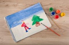 Kinderpapierbild von Weihnachten und von Farben, Bürsten auf Tabelle Stockfoto