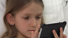 Kinderporträt, das Tablet-PC im Bett-Mädchen sich entspannt beim Schlafzimmer-Schlafen 4K nicht spielt stock footage