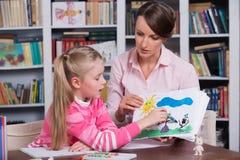 Kinderpsychologe bespricht sich, ein kleines Mädchen zu zeichnen Stockbild