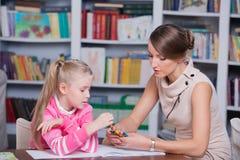Kinderpsychologe mit einem kleinen Mädchen stockbild