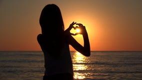 Kinderschattenbild auf Strand, Liebe unterzeichnen im Sonnenuntergang auf Valentinstag-Herzen formen 4K stock video