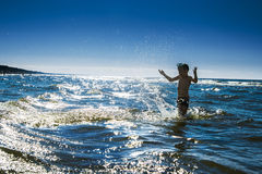 Kinderschattenbild und -wasser spritzt im Meer. Sommerzeit vacati Lizenzfreie Stockfotografie