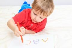 Kinderschreibensbuchstaben lizenzfreie stockfotos