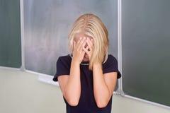 Kinderschulmädchen bedeckte ihr Gesicht mit ihren Händen im Klassenzimmer nahe dem Brett Lernte keine Lektion oder ein Umkippen I stockbild