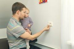 Kindersicherheit zu Hause Vater schützen Kind vor elektrischer Verletzung lizenzfreies stockbild