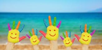 Kindersmileyhände auf einem Strand Stockfoto