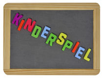 Kinderspiel in colored letters on slate Royalty Free Stock Photos