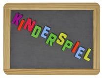 Kinderspiel in farbigen Buchstaben auf Schiefer Lizenzfreie Stockfotos