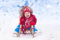 Kinderspiel im Schnee Winterpferdeschlittenfahrt für Kinder lizenzfreies stockbild