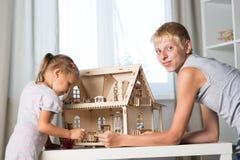 Kinderspiel mit einem Puppenhaus Lizenzfreie Stockbilder