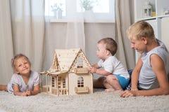 Kinderspiel mit einem Puppenhaus Stockbild