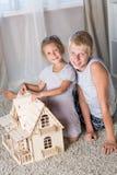 Kinderspiel mit einem Puppenhaus Lizenzfreie Stockfotos