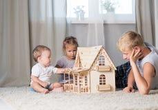 Kinderspiel mit einem Puppenhaus Lizenzfreies Stockfoto