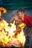 Kinderspiel mit Feuer im Grill Stockfotos