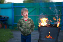 Kinderspiel mit Feuer im Grill Stockfotografie