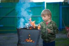 Kinderspiel mit Feuer im Grill Lizenzfreie Stockfotos