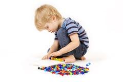 Kinderspiele mit einem Mosaik Stockfotos