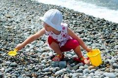 Kinderspiele mit einer Wanne und einer Schaufel laufen leer Stockbild
