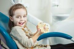 Kinderspiele mit künstlichem menschlichem Kiefer im Zahnarztstuhl Stockfoto