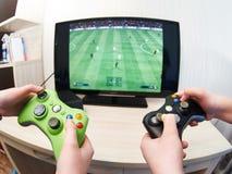 Kinderspielen auf der Spielkonsole, zum des Fußballs zu spielen Lizenzfreie Stockfotografie
