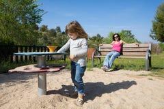 Kinderspielen und -mutter beim Bankaufpassen Stockbild
