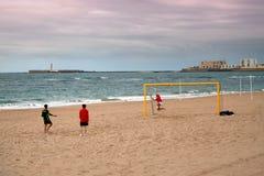 Kinderspielfußball durch das Meer im regnerischen Wetter lizenzfreie stockbilder