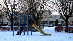 Kinderspielplatz mit dem Dia umfasst im Schnee während des Winters stockfotografie