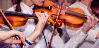 Kinderspielviolinen während des Konzerts Ausführung der klassischen Musik auf Violins_ lizenzfreie stockbilder
