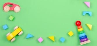 Kinderspielwaren-Hintergrundrahmen mit dem Baby, das Ringpyramide, hölzernes Auto und bunte Blöcke auf grünem Hintergrund stapelt stockfotografie