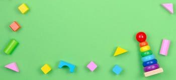 Kinderspielwaren-Hintergrundrahmen mit dem Baby, das Ringpyramide und bunte Bl?cke auf gr?nem Hintergrund stapelt stockbild