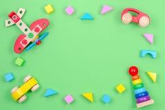 Kinderspielwaren-Hintergrundrahmen mit hölzerner Fläche, Autos, Baby, das Ringpyramide und bunte Blöcke auf grünem Hintergrund st lizenzfreies stockfoto