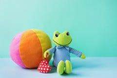 Kinderspielwaren-kleiner Plüsch-Frosch, der rotes Herz-mehrfarbiges Textilweichen Ball auf blaues Grün-Hintergrund hält Fahne Pla Stockbilder