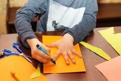 Kinderspur um eine Hand auf Papier mit Zeichenstiften Stockfoto