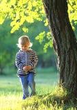 Kinderstand an einem Baum im Herbst Stockfoto