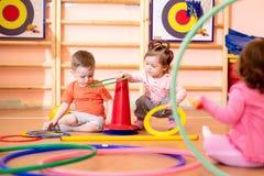 Kindertagesstättenbaby-Gruppenspiel mit Ringen in der Turnhalle stockfoto
