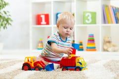Kindertagesstättenbaby spielt die Block- und Autospielwaren, die zuhause auf Teppich sitzen stockfotografie