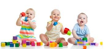 Kindertagesstättenbabys, die mit den Spielwaren lokalisiert auf Weiß spielen lizenzfreie stockfotografie