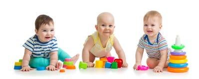 Kindertagesstättenbabys, die mit den Spielwaren lokalisiert auf weißem Hintergrund spielen lizenzfreies stockfoto