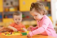 Kindertagesstättenbabys spielen mit Plasticine im Kindergarten lizenzfreie stockbilder